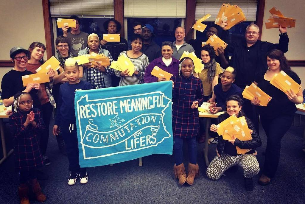 """Group of people stand behind hand painted sign that says """"Restore Meaningful Commutation for Lifers"""", holding envelopes addressed and ready to mail."""