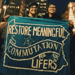 "Devon and Cat hold a banner ""Restore Meaningful Commutation for Lifers"" at the Fight for 15 labor march."