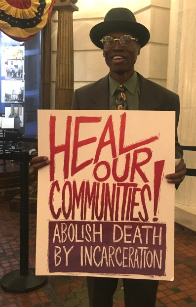 "Atilla holding ""Heal our Communities! Abolish Death by Incarceration sign"