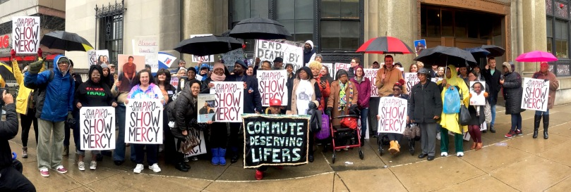 """Large group of people standing outside in the rain with umbrellas and holding signs that say """"shapiro show mercy"""" """"commute deserving lifers"""""""